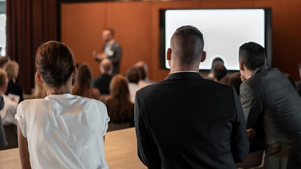 Zwei Zuhörer an einem Vortrag